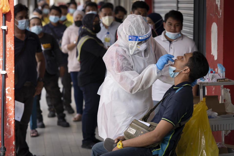 A doctor collects a sample for a coronavirus test outside a clinic in Kajang on the outskirts of Kuala Lumpur, Malaysia, Friday, Oct. 23, 2020. Malaysia restricted movements in its biggest city Kuala Lumpur, neighbouring Selangor state and the administrative capital of Putrajaya from Wednesday in an attempt to curb a sharp rise in coronavirus cases. (AP Photo/Vincent Thian)