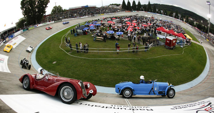 A 1929 Bugatti 49 (R) sports car driven by Joerg Koenig drives ahead of Alexander Vonow in a 1939 Alfa Romeo 8C 2900 sports car (front L) car through a steep turn during a race demonstration at the Offene Rennbahn cycling track in Zurich's Oerlikon suburb July 26, 2011. (REUTERS/Arnd Wiegmann)