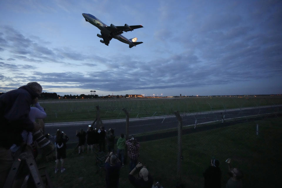 People watch Air Force One, carrying U.S. President Joe Biden and first lady Jill Biden, take off from RAF Mildenhall, near Bury St. Edmunds, in eastern England, to go to Cornwall for the G7 summit, Wednesday, June 9, 2021. (AP Photo/Matt Dunham)