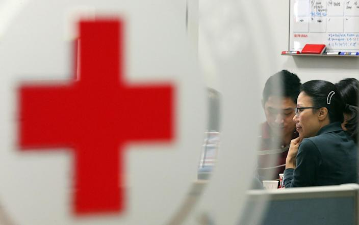Employees of the Red Cross work at the Korean Red Cross headquarters in Seoul, South Korea, Saturday, Sept. 21, 2013. North Korea on Saturday indefinitely postponed reunions of families separated by the 1950-53 Korean War scheduled to start Wednesday, an apparent setback after weeks of improving ties following springtime threats of war. (AP Photo/Yonhap, Park Dong-ju) KOREA OUT