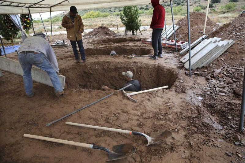 Men dig graves for Rhonita Miller, 30, and four of her young children Krystal and Howard, and twins Titus and Tiana, who were murdered by drug cartel gunmen, before their burial at a cemetery in LeBaron, Chihuahua state, Mexico, Friday, Nov. 8, 2019. A total of three women and six of their children, from the extended LeBaron family, were gunned down in a cartel ambush while traveling along Mexico's Chihuahua and Sonora state border on Monday. (AP Photo/Marco Ugarte)