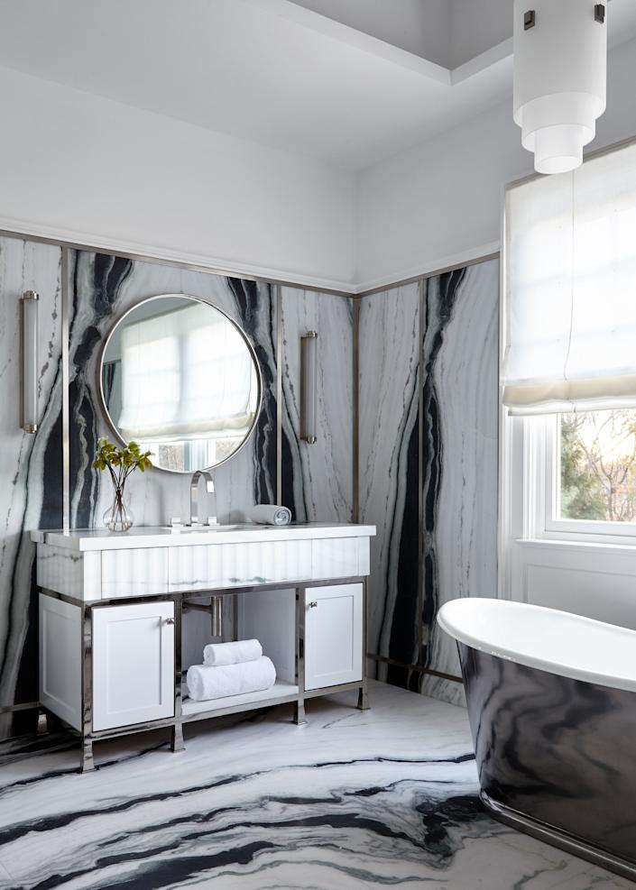 "<div class=""caption""> Strategically placed wainscoting introduces airiness and a visual boundary for the vibrant panda marble on display in the master bath. Sconces by <a href=""https://collierwebb.com/"" rel=""nofollow noopener"" target=""_blank"" data-ylk=""slk:Collier Webb"" class=""link rapid-noclick-resp"">Collier Webb</a> and a pendant by <a href=""https://www.perzel.fr/en/"" rel=""nofollow noopener"" target=""_blank"" data-ylk=""slk:Jean Perzel"" class=""link rapid-noclick-resp"">Jean Perzel</a> create an intimate glow that bounces off the custom <a href=""https://www.sabaxter.com/"" rel=""nofollow noopener"" target=""_blank"" data-ylk=""slk:SA Baxter x Sara Story Design"" class=""link rapid-noclick-resp"">SA Baxter x Sara Story Design</a> hardware and metallic bathtub finish. </div>"