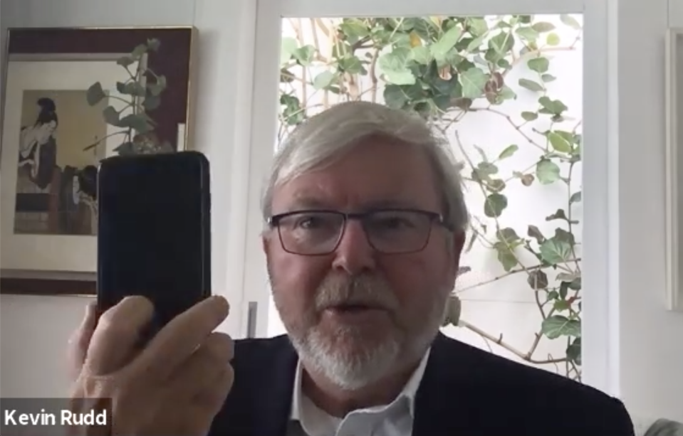 Kevin Rudd seen holding up his iPhone with the contact tracing app.