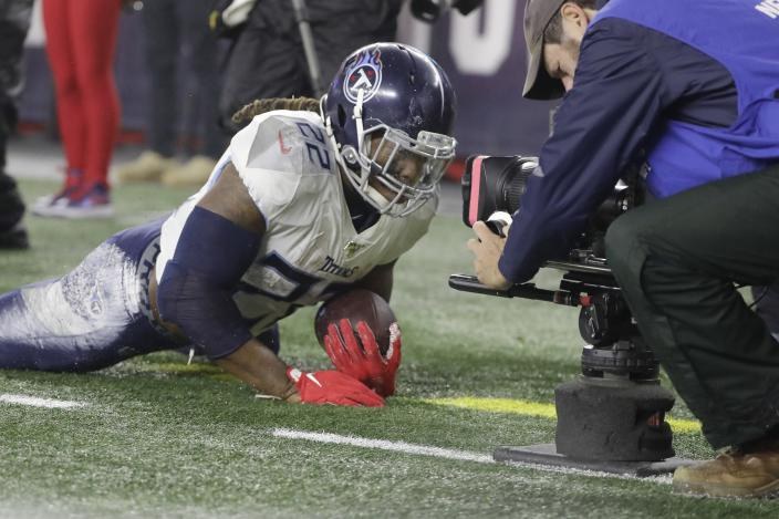 A cameraman focuses on Tennessee Titans running back Derrick Henry, after he landed out of bounds following a run in the first half of an NFL wild-card playoff football game against the New England Patriots, Saturday, Jan. 4, 2020, in Foxborough, Mass. (AP Photo/Steven Senne)