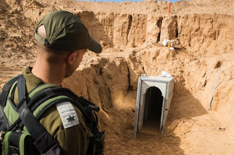 An Israeli officer walks near the entrance of a cross-border tunnel that Israel says was dug by the Islamic Jihad group from the Gaza Strip, on January 18, 2018 (AFP Photo/JACK GUEZ)