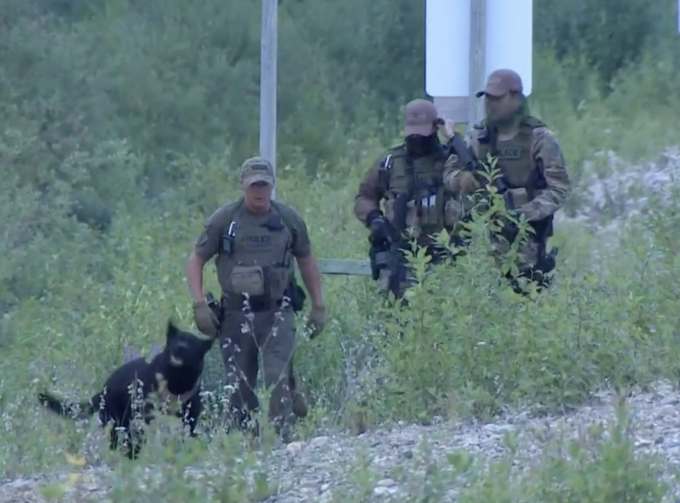 Canadian authorities armed with guns and a dog search for suspects Kam McLeod and Bryer Schmegelsky.