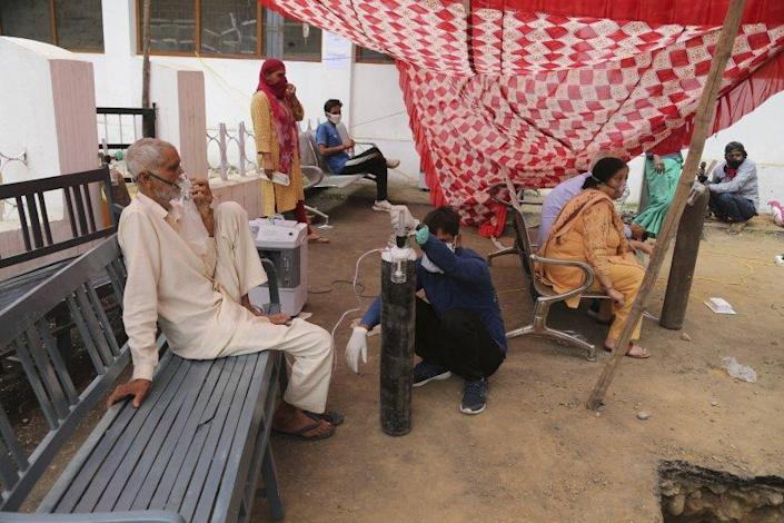 COVID-19 patients receive oxygen outside a government run hospital in Jammu, India, Wednesday, May 12, 2021. (AP Photo/Channi Anand)