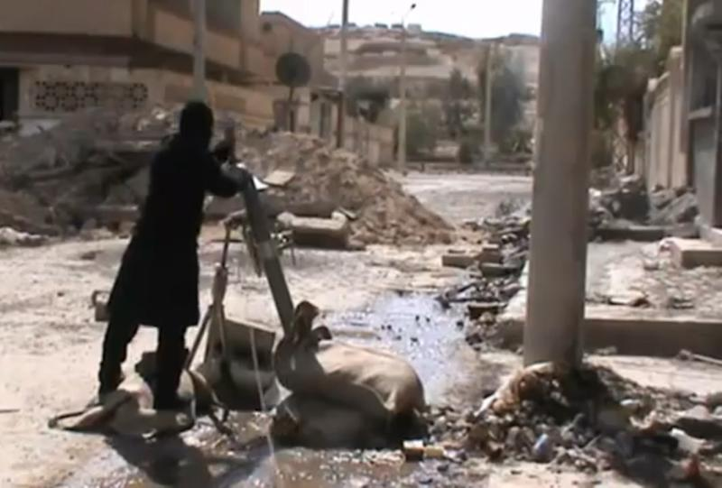 In this Sunday, March 24, 2013 image taken from video obtained from the Ugarit News, which has been authenticated based on its contents and other AP reporting, Free Syrian Army fighters drops a shell into a firing tube, in Damascus countryside, Syria. (AP Photo/Ugarit News via AP video)