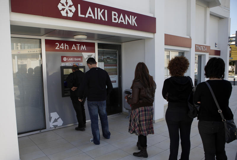 People queue to use an ATM machine outside of a Laiki Bank branch in Larnaca, Cyprus, Saturday, March 16, 2013. Many rushed to cooperative banks which are open Saturdays in Cyprus after learning that the terms of a bailout deal that the cash-strapped country hammered out with international lenders includes a one-time levy on bank deposits. The move, decided in an extraordinary meeting of the finance ministers of the 17-nation eurozone in the early hours Saturday, is a major departure from established policies. Analysts have warned that making depositors take a hit threatens to undermine investors' confidence in other weaker eurozone economies and might possibly lead to bank runs. (AP Photo/Petros Karadjias)