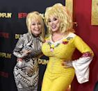 """<p>Are we seeing double? For the premiere of Netflix's <em>Dumplin</em>', Parton poses with <a href=""""https://archive.sltrib.com/article.php?id=3251188&itype=CMSID"""" rel=""""nofollow noopener"""" target=""""_blank"""" data-ylk=""""slk:impersonator Jason CoZmo"""" class=""""link rapid-noclick-resp"""">impersonator Jason CoZmo</a>. </p>"""