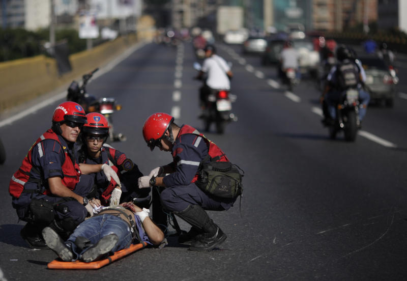 In this photo taken Wednesday, June 26, 2013, Venezuelan firefighters give first aid to an unidentified man after he lost control of his motorcycle, in Caracas, Venezuela. Venezuela is the world's third-worst country for motor vehicle-related deaths with 37.2 per 100,000 inhabitants, according to a World Health Organization global road safety study published this year. It's not clear how many of those involved motorcycles. But news of accidents are a constant on the radio, and one recent report said the more than a dozen hospitals in the capital treat at least 100 motorcycle injuries a week - apiece. (AP Photo/Ariana Cubillos)