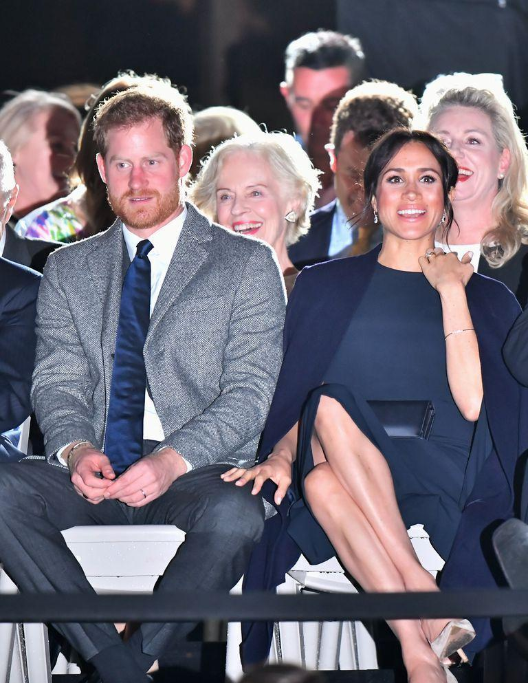 """<p>Harry and Meghan dressed up for the opening of the Invictus Games. The Duchess <a href=""""https://www.townandcountrymag.com/style/fashion-trends/a23937214/meghan-markle-stella-mccartney-invictus-games-opening-ceremony-sydney-australia/"""" rel=""""nofollow noopener"""" target=""""_blank"""" data-ylk=""""slk:chose a navy a Stella McCartney cape dress"""" class=""""link rapid-noclick-resp"""">chose a navy a Stella McCartney cape dress</a>, a style she previously wore to a concert for the Queen's birthday, with matching coat by Gillian Anderson for Winser London.</p>"""
