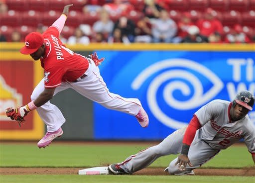 Washington Nationals' Roger Bernadina (2) advances to second as Cincinnati Reds second baseman Brandon Phillips (4) is pulled off the bag by a wide throw in the first inning of a baseball game on Sunday, May 13, 2012, in Cincinnati. Bernadina advanced on a fly-out by Ryan Zimmerman. (AP Photo/Al Behrman)