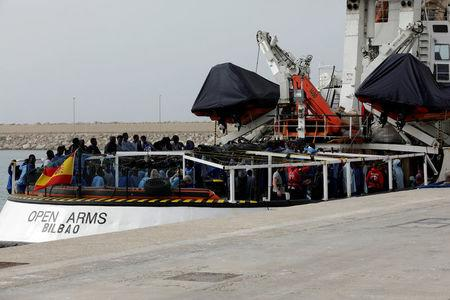 FILE PHOTO: Migrants wait to disembark from Spanish NGO Proactiva Open Arms in the Sicilian harbour of Pozzallo, Italy, March 17, 2018. Picture taken March 17, 2018. REUTERS/Antonio Parrinello/File Photo