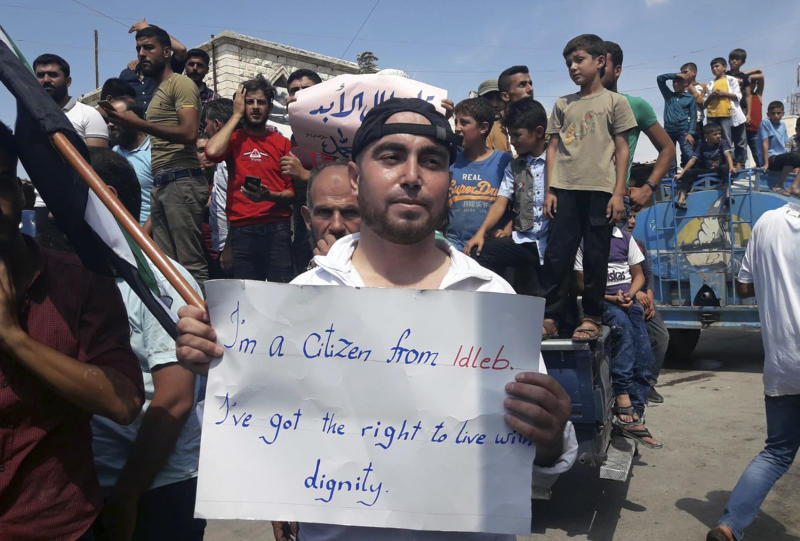This image courtesy of Mustafa Alabdullah, an activist and resident of Idlib, shows a protester holding a placard, in Harim, a town in Idlib province, Syria, Friday, Sept 7, 2018. The rallies were part of a day of protests against Syrian President Bashar Assad and his troops' imminent offensive against Idlib, the last bastion of rebels in Syria. The Friday rallies came as Presidents of Iran, Turkey and Russia are meeting in Tehran to discuss the war in Syria. The summit may determine whether diplomacy halts any military action in Idlib and its surrounding areas, home to more than 3 million people. Nearly half of the area's residents are already displaced from other parts of Syria and have refused to reconcile with the Syrian government. (Courtesy of Mustafa Alabdullah via AP)