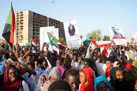Sudanese demonstrators celebrate after Defence Minister Awad Ibn Auf stepped down as head of the country's transitional ruling military council, as protesters demanded quicker political change, near the Defence Ministry in Khartoum