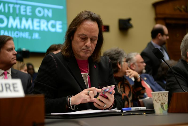 T-Mobile US CEO John Legere checks his phone before testifying before a U.S. House Committee on Energy and Commerce Subcommittee hearing in Washington, U.S. February 13, 2019. REUTERS/Erin Scott