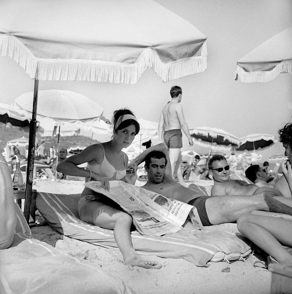 <p>Film director Roger Vadim and actress Catherine Deneuve rest under a parasol in Saint-Tropez, France. </p><p>Other celebrity visitors this year: Brigitte Bardot.</p>