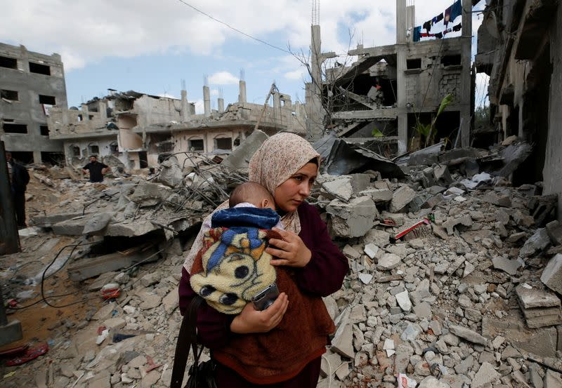 A Palestinian woman carries her child amid the rubble of their houses destroyed by Israeli air strikes