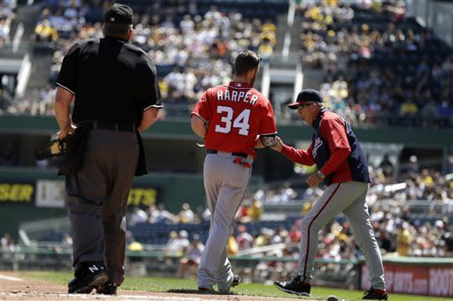 Washington Nationals manager Davey Johnson, right, charges out of the dugout after Nationals' Bryce Harper (34) was ejected by third base umpire John Hirschbeck (not shown) for arguing a called third strike in the first inning of a baseball game against the Pittsburgh Pirates in Pittsburgh, Sunday, May 5, 2013. Home plate umpire Bob Davidson, left, appealed the strike call to third base umpire Hirschbeck. (AP Photo/Gene J. Puskar)