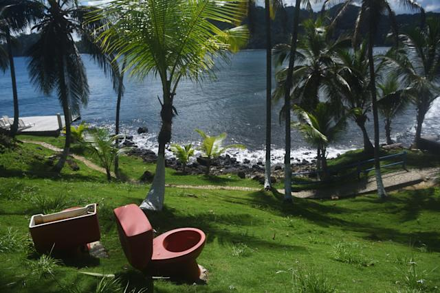 <p>A red toilet in the garden of a hotel in Isla Grande, outside of Panama City, Panama. (Photo: Rodrigo Arangua/AFP/Getty Images) </p>
