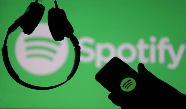 A smartphone and a headset are seen in front of a screen projection of Spotify logo. (Photo: Reuters/Dado Ruvic/Illustration)