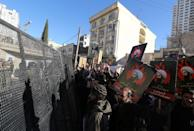 Iranian riot police block a street leading to the Saudi embassy as protesters hold portraits of prominent Shiite Muslim cleric Nimr al-Nimr during a demonstration against his execution by Saudi authorities, on January 3, 2016, in Tehran (AFP Photo/Atta Kenare)