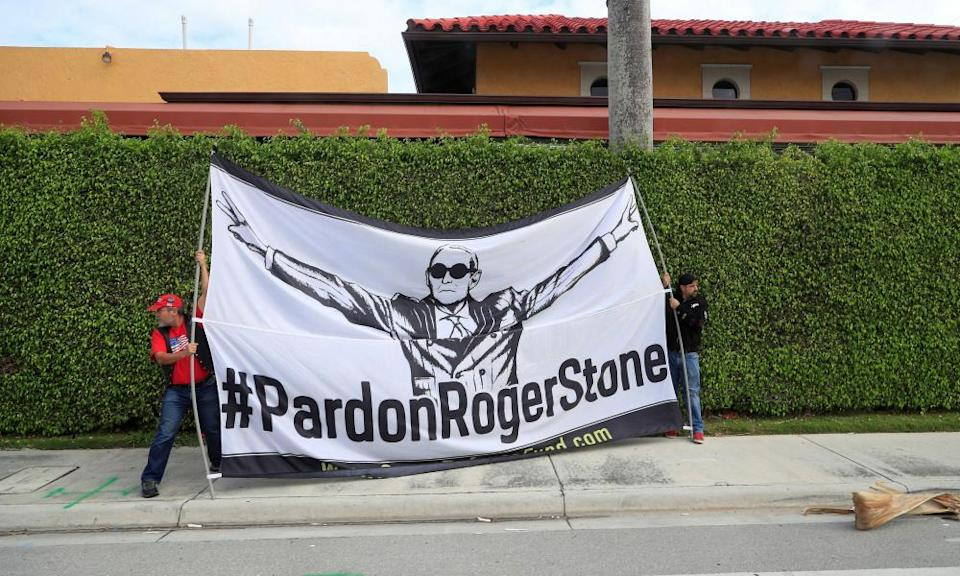 Demonstrators display a banner urging Donald Trump to pardon his former campaign adviser Roger Stone, as the presidential motorcade passes through West Palm Beach, Florida, in March.