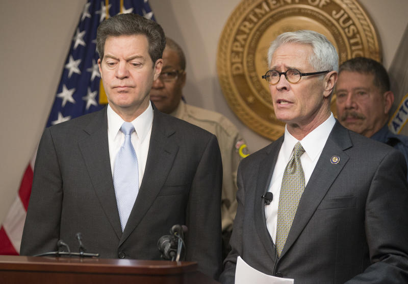 Kansas Gov. Sam Brownback, left, listens as U.S. Attorney Barry Grissom announces the arrest of Terry Lee Loewen, 58, of Wichita, Kan., during a news conference on Friday, Dec. 13, 2013, in Witchita, Kan. Grissom said Loewen was arrested Friday morning at Mid-Continent regional airport where he planned to drive a car that he believed was full of explosives into a terminal at the airport. (AP Photo/The Wichita Eagle, Travis Heying)