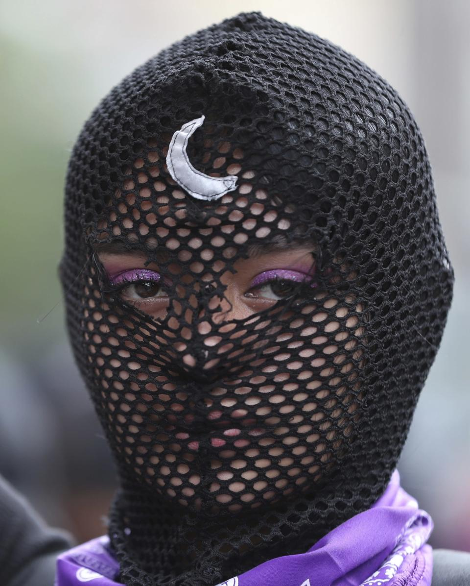 A masked woman takes part in an International Women's Day protest in Bogota, Colombia, Monday, March 8, 2021. (AP Photo/Fernando Vergara)