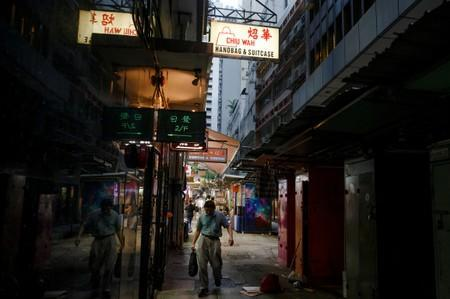 FILE PHOTO: A man walks between stalls in an alley in the Central business district in Hong Kong