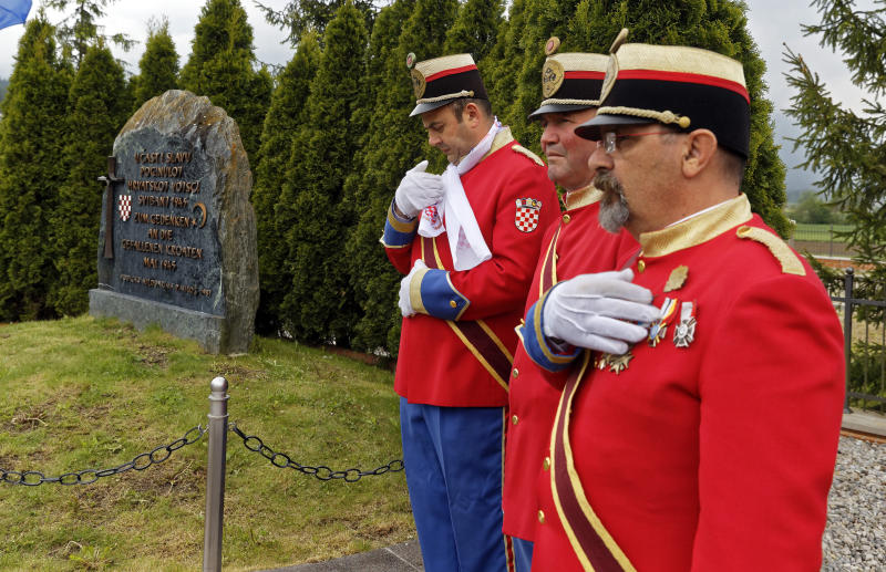 Honor guards stand next to a monument during a liturgical service for victims of the end of WWII events in Bleiburg, southern Austria, Saturday, May 18, 2019. Thousands of Croatian far-right supporters have gathered in a field in southern Austria to commemorate the massacre of pro-Nazi Croats by communists at the end of World War II. (AP Photo/Darko Bandic)