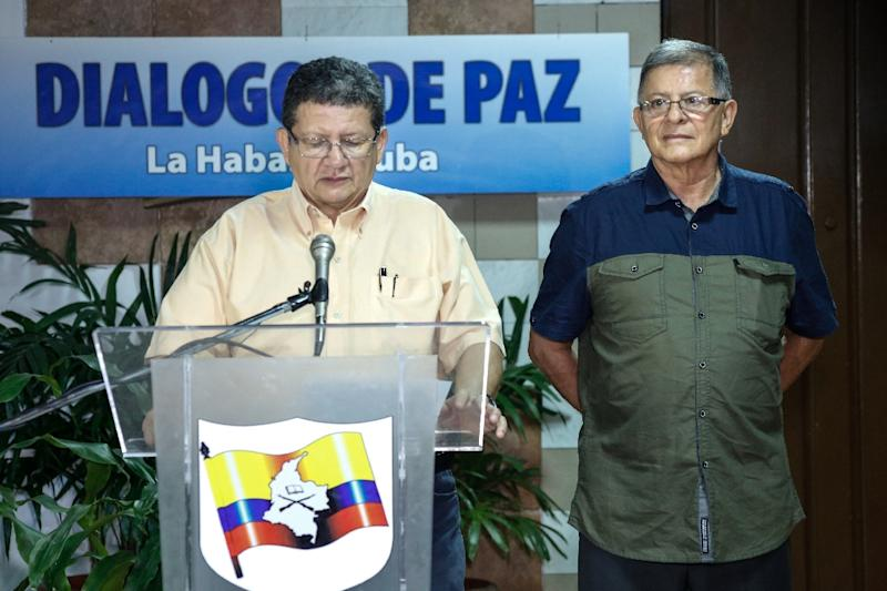 A picture released by the FARC-EP delegation, shows leftist guerrilla commander Pablo Catatumbo (L) reading a statement as commander Ricardo Tellez listens, during the peace talks with the Colombian Government in Havana, on August 24, 2015