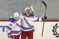 New York Rangers defenseman Brendan Smith (42) celebrates with Rangers defenseman Adam Fox (23) after scoring the Rangers' fifth goal during the third period of an NHL hockey game against the New Jersey Devils, Thursday, March 4, 2021, in Newark, N.J. The Rangers defeated the Devils 6-1. (AP Photo/Kathy Willens)