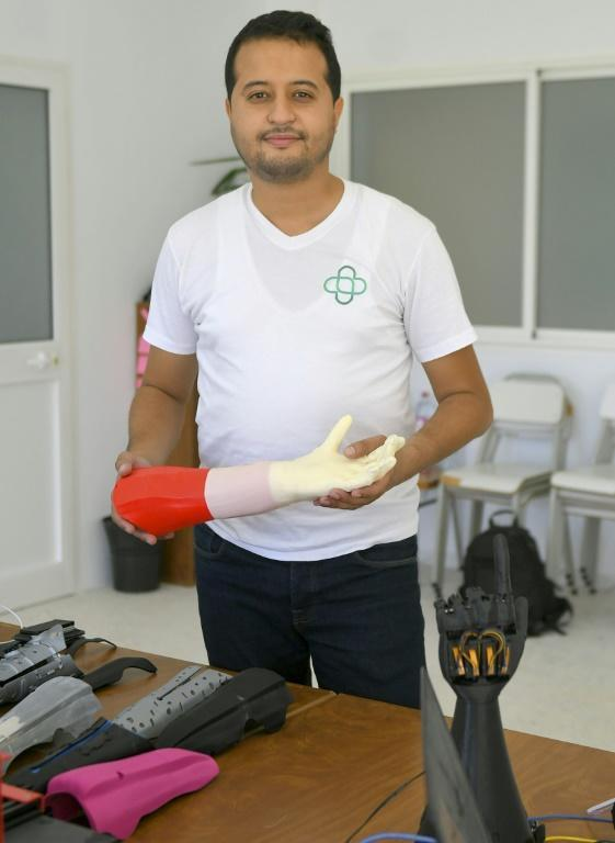 Tunisian engineer Mohamed Dhaouafi, who launched his start-up in 2017 from his parents' home, holds a prototype of an artificial hand