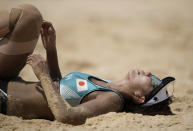 Megumi Murakami, of Japan, lays in the sand during a women's beach volleyball match against Switzerland at the 2020 Summer Olympics, Wednesday, July 28, 2021, in Tokyo, Japan. (AP Photo/Felipe Dana)