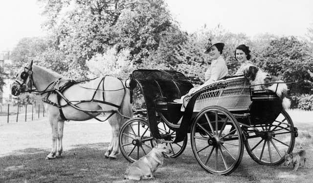 Princess Elizabeth and Queen Elizabeth, seated in a horse drawn carriage in the garden at Windsor Castle (Lisa Sheridan/PA)