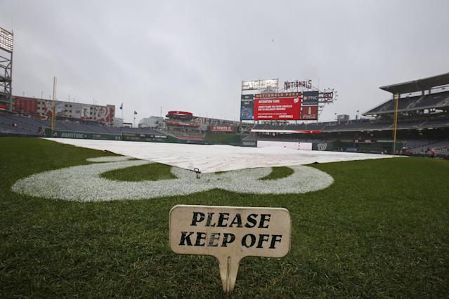 The field is covered before an exhibition baseball game between the Washington Nationals and the Detroit Tigers at Nationals Park Saturday, March 29, 2014, in Washington. The game was canceled due to weather. (AP Photo/Alex Brandon)