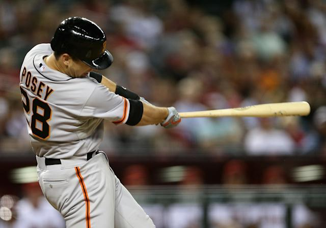 PHOENIX, AZ - MARCH 31: Buster Posey #28 of the San Francisco Giants hits a two run home-run against the Arizona Diamondbacks during the ninth inning of the Opening Day MLB game at Chase Field on March 31, 2014 in Phoenix, Arizona. (Photo by Christian Petersen/Getty Images)