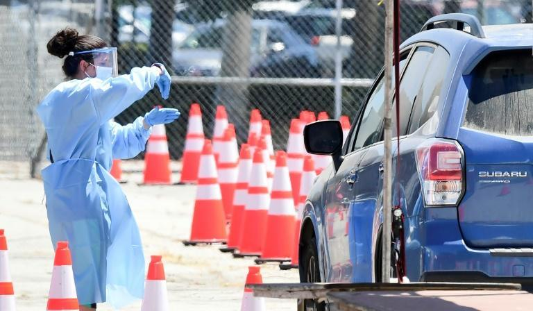 A volunteer gestures instructions to a driver at a COVID-19 test site on July 30, 2020 in the Panoramic City neighborhood of Los Angeles, California, where cases continue to spike