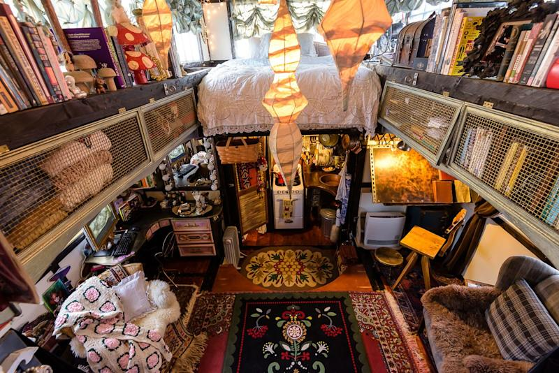 Sweaters, books, and favorite objects are stored in custom drawers and trunks around the tiny house.