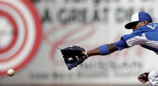Kansas City Royals shortstop Alcides Escobar cannot reach a ball that went for a single by Colorado Rockies' Eric Young Jr. during the fourth inning in an exhibition spring training baseball game Tuesday, March 19, 2013, in Surprise, Ariz. (AP Photo/Gregory Bull)
