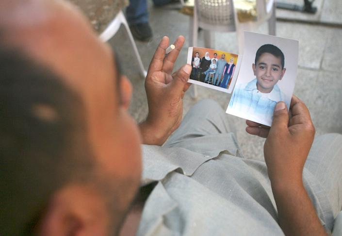Mohammed Hafiz looks at photos of his 10-year-old son in Baghdad on Oct. 4, 2007. The boy died after the attack on Iraqi civilians by U.S. Blackwater contractors on Sept. 16, 2007. (Photo: AP Photo/Khalid Mohammed)