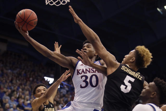 Kansas' Ochai Agbaji (30) gets past Colorado's D'Shawn Schwartz (5) to shoot during the first half of an NCAA college basketball game Saturday, Dec. 7, 2019, in Lawrence, Kan. (AP Photo/Charlie Riedel)