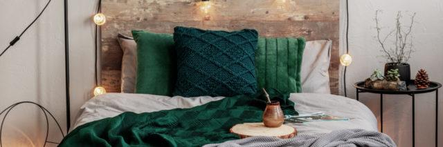 Photo of bedroom. Green pillows, a green and grey blanket draped over bed. Wooden headboard with yellow string lights. Cup of tea sitting on bed