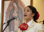 Mariachi Herencia de Cuco Del Cid's Adelys LaTurco sings for parishioners during a morning Mass at Most Holy Trinity Parish Sunday, Aug. 18, 2021 in Tucson. (AP Photo/Darryl Webb)