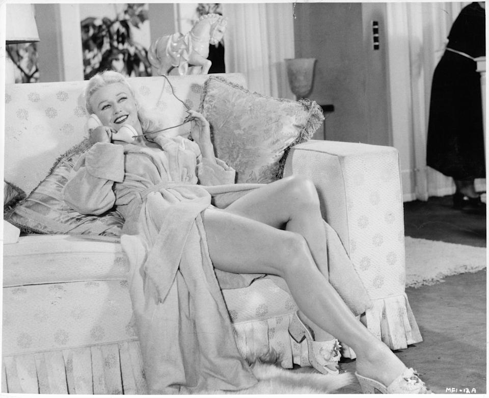 """Rogers on the phone wearing a bathrobe in a scene from the film """"Twist of Fate,"""" 1954."""