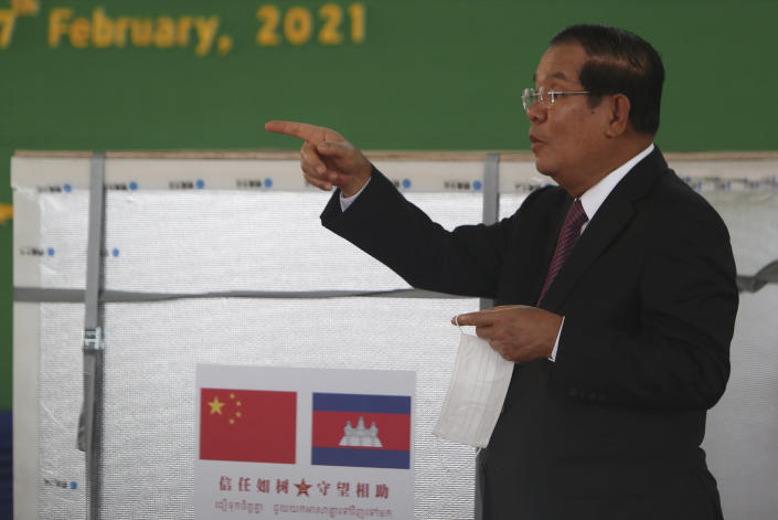 """Cambodian Prime Minister Hun Sen gestures during a handover ceremony at Phnom Penh International Airport, in Phnom Penh, Cambodia, Sunday, Feb. 7, 2021. Cambodia on Sunday received its first shipment of COVID-19 vaccine, a donation of 600,000 doses from China, the country's biggest ally. Beijing has been making such donations to several Southeast Asian and African nations in what has been dubbed """"vaccine diplomacy,"""" aimed especially at poorer countries like Cambodia. (AP Photo/Heng Sinith)"""