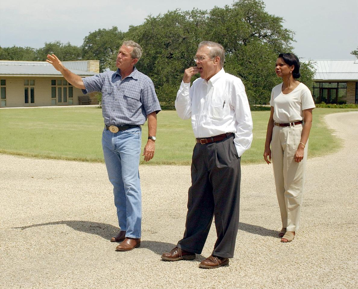 U.S. President George W. Bush (L) gesturs while answering questions from the media as U.S. Secretary of Defense Donald Rumsfeld (C) and U.S. National Security Advisor Condoleezza Rice stand nearby at Bush's ranch house August 8, 2003 near Crawford, Texas. President Bush stated that people responsible for attacking U.S. troops in Iraq are slowly being wiped out.  (Photo by Rod Aydelotte-Pool/Getty Images)