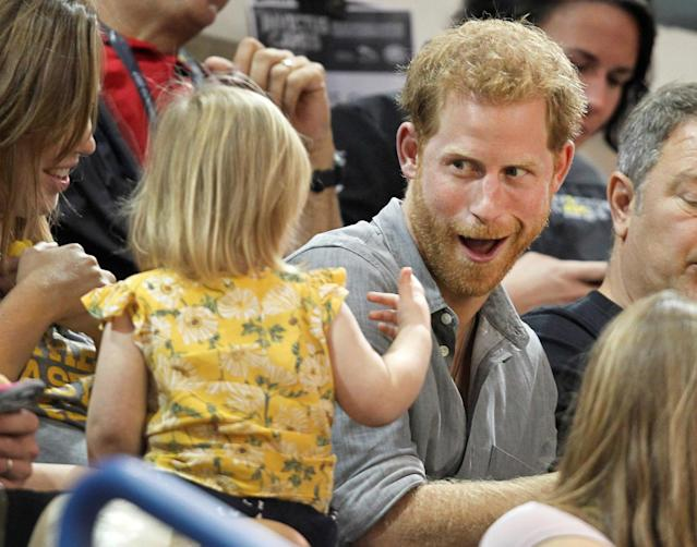 Britain's Prince Harry, patron of the Invictus Games Foundation, shares popcorn with a child while attending the Sitting Volleyball competition at the games in Toronto, Ontario, Canada, September 27, 2017. REUTERS/Fred Thornhill TPX IMAGES OF THE DAY